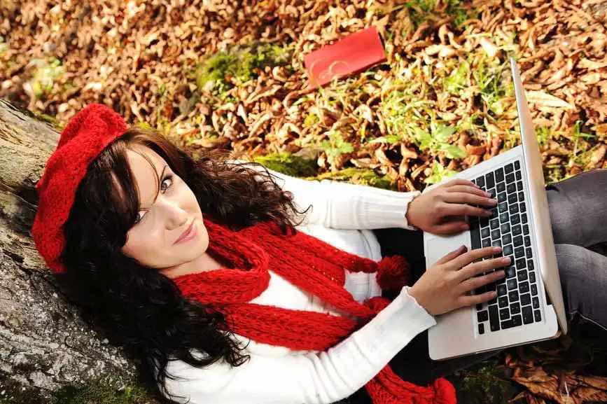 Szép őszi tájban, szép lány internetezik.